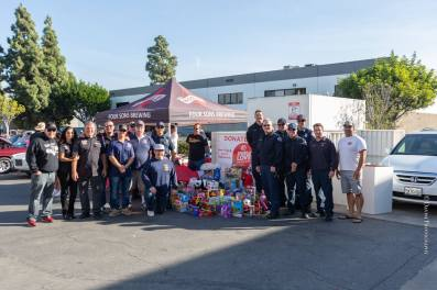 The team from Hedman and show staff pose with the Huntington Beach Fire Department and Firefighter Association members at the end of a great show that collected scores of toys for the Spark of Love program.